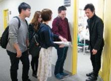 研究室の前で会話する教員と学生の写真
